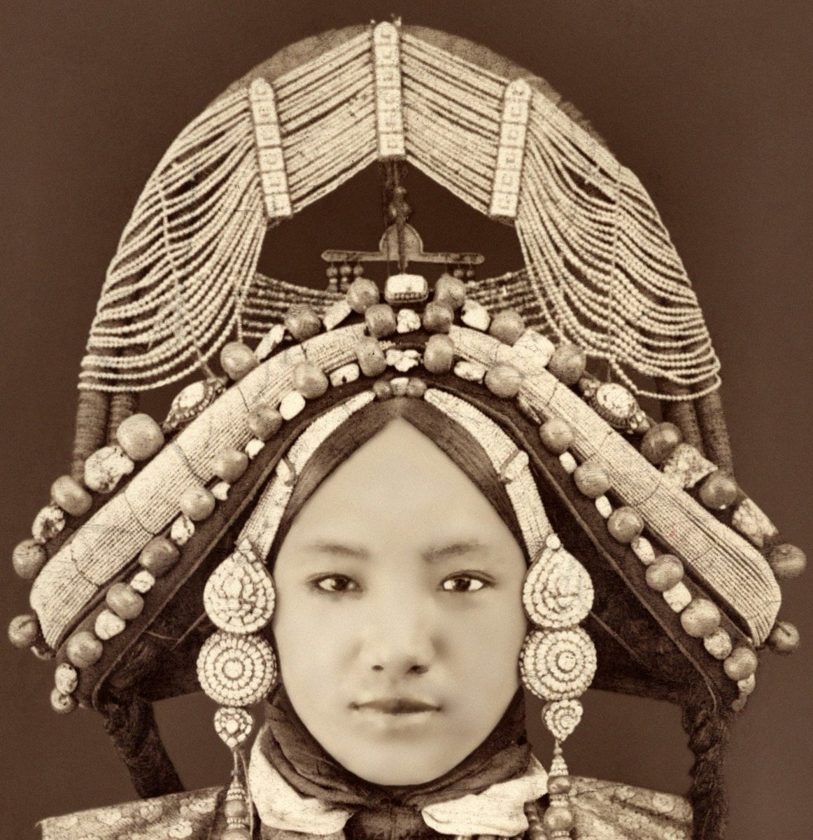 A Tibetan woman, from 1879: crown-shaped ornament studded with precious stones and pearls of every size. Pearl necklaces, strings of amber and coral hung over her breast, and her clothes were of the richest Chinese satin brocades and the finest native cloth.  Creative Commons Attribution 2.0 Generic via Wikipedia.