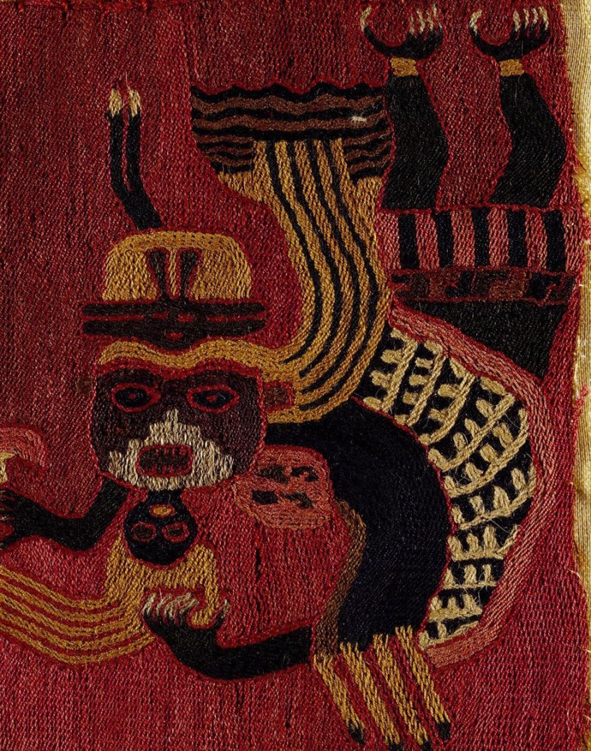 This small panel, originally part of a garment or burial cloth, is typical of the embroideries found. It shows a shaman or witch doctor clutching a severed head in one hand and an axe and sacrificial knife in the other. This ferocious 'trophy-head' cult also featured cats and monkeys. The contorted shape of the main figure, whose head almost touches the ground, and the grimace on the face of the beheaded victim adds to the startling nature of the design.  The embroidery is in stem stitch in wool on a cotton background. The makers of these early embroideries were the first in Peru to use wool extensively and realise its potential for creating designs (wool can be dyed easily and so a large variety of colours are possible).  ©Victoria & Albert Museum, London