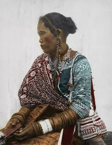 """From the original description: """"The red and yellow skirt belongs only to the wife of a man killer but the rest of the costume is typical of the Bagobo women, especially the bell-decorated bag worn from the shoulder. The cheap European fan in her hand contrasts strangely with the curious bead pendant which hangs from ear to ear."""" DEAN C. WORCESTER/National Geographic Creative"""