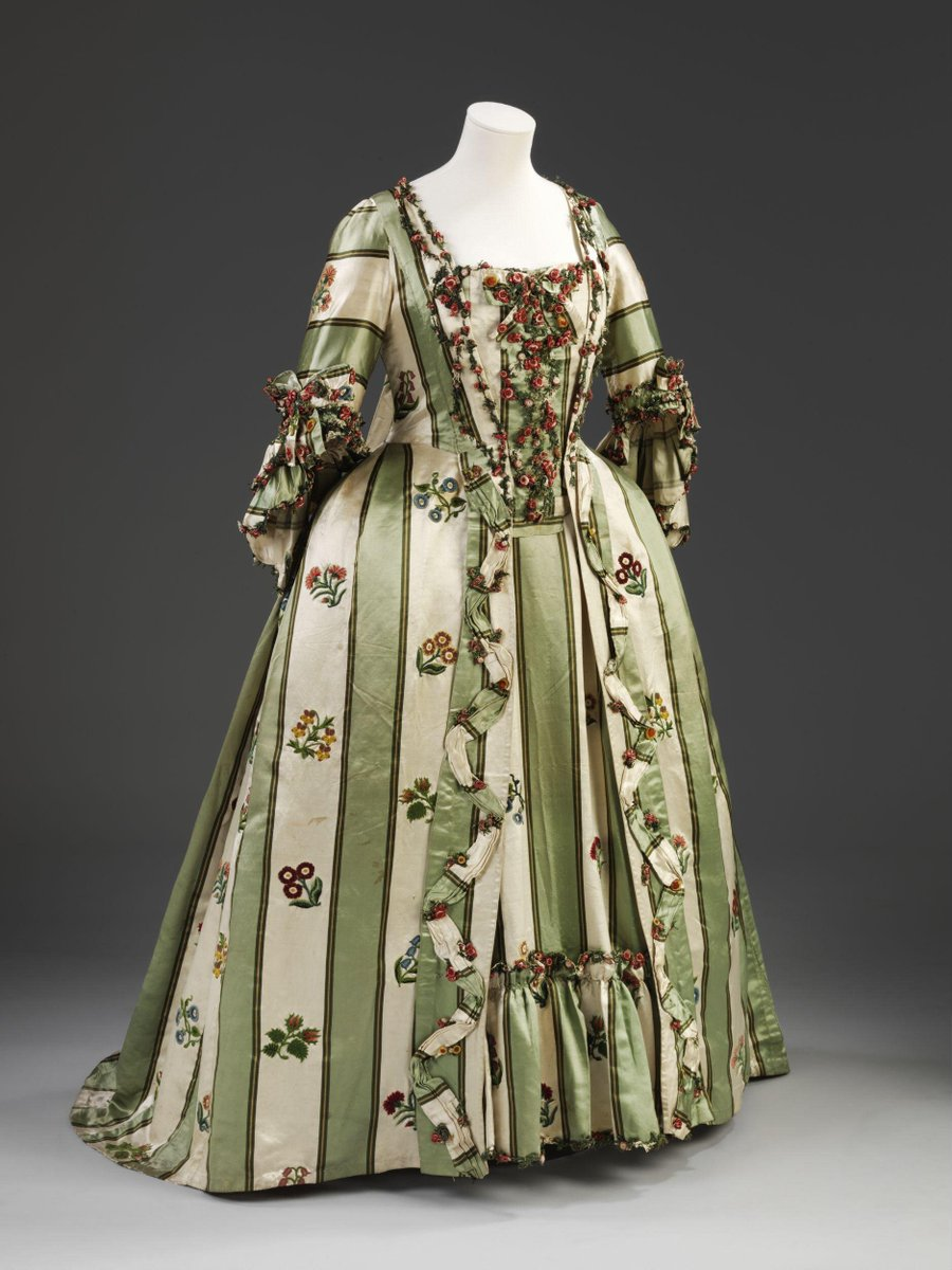 ©Victoria and Albert Museum, London - A woman's sack with a stomacher and petticoat made of striped green and white satin trimmed with a fly fringe and embroidered in chenille with floral sprays. These include pansies, morning glories, ranunculas, carnations and harebells and rosebuds. The sack is open at the front with elbow-length sleeves with double, scalloped sleeve ruffles. The bodice and sleeves are lined with linen; the back of the lining in two pieces and fastened with linen tape ties. The back has two, double box pleats extending shoulder to hem, with the front skirts pleated into the waistseam. The sack is made of 6 widths of silk, with 2 triangular gores on each front side. The robings of the bodice are seamed a the waist to the front skirts. The skirt robings are trimmed with a pleated band of silk arranged in a zig-zag down the front. A fringe of elaborately looped silk flowers and floss knots is arranged in a zig-zag down the bodice robings. It edges the sleeve ruffles.