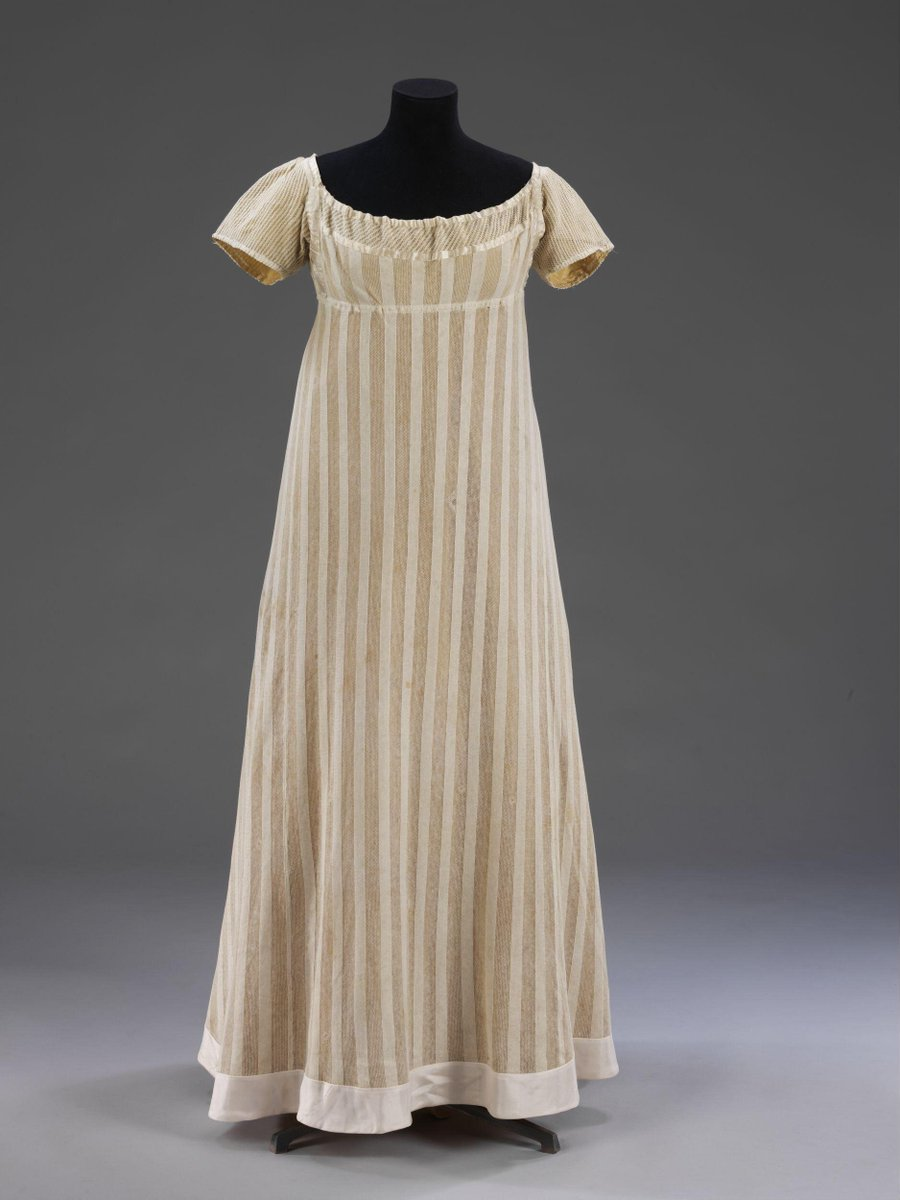 ©Victoria and Albert Museum, London- Dress made of warp-knitted fabric, probably cotton. With a pattern of alternating stripes of close 'plain' knitting and open work. The sleeves and a band inserted around the neck are also in knitted cotton with a smaller pattern of alternating plain and open work.    Low square neck and short sleeves, and with a frilled yellow silk ribbon epaulette and a yellow ribbon draw string through the binding at the sleeve border. Yellow ribbon bands are mounted over the white silk band trim neck opening, the top of the bodice and the sides of the front. The waist is high and the skirt is attached to the high waist except at the centre back where it is slightly gathered. The skirt is cut with a centre front, centre back and two wedge-shaped side panels. The hem is bordered with a gathered yellow silk band. The dress fastens at the centre back with a yellow silk ribbon through the neck, and a cord and a tape through the waist attached from the side seam.