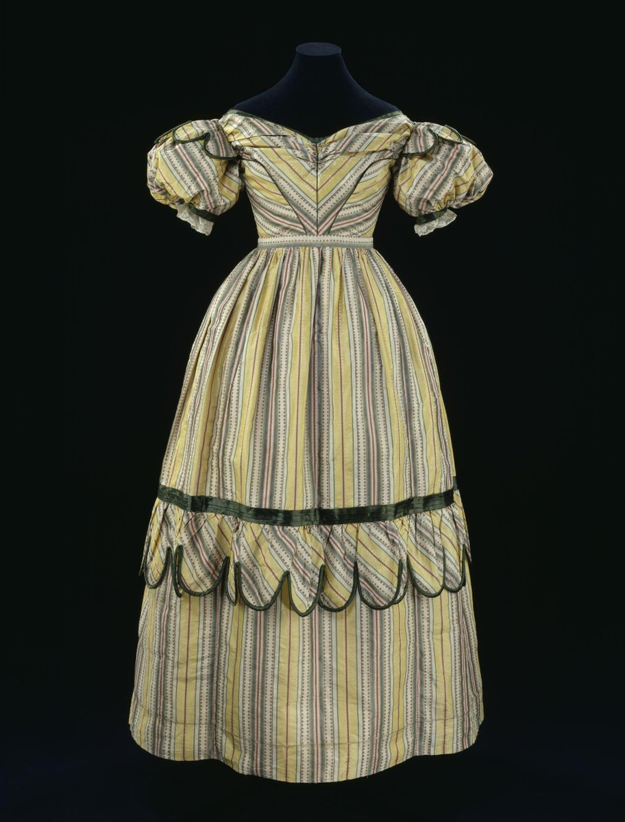 ©Victoria and Albert Museum, London - Evening dress made of brocaded silk tobine trimmed with silk satin and lined with cotton. Made from warp striped tobine in yellow cream and green with red warp patterns. The neck is low and oval, and the high waisted bodice is gauged in the centre front. The sleeves are short and full puffed, covered with lobed epaulets. The skirt is gathered to the bodice, and the gauging is slightly tighter at the centre back. Just below knee level is a wide band of gathered trimming, of matching material headed by a pleated band of green satin, and the lobed edges are bound with the same. Green satin is used to bind the neck, edge the epaulets and pipe the bodice seams. The dress fastens at the centre back with a false fastening of small self covered buttons, and the actual fastening was probably hook and eyes. The existing fastenings are replacements.