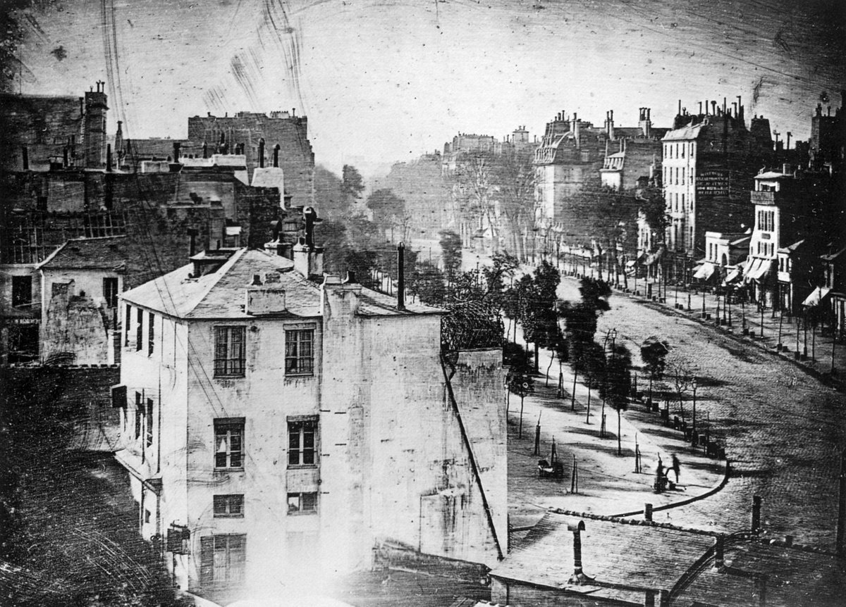 From the Wikipedia entry: View of the Boulevard du Temple, taken by Daguerre in 1838 in Paris, includes the earliest known photograph of a person. The image shows a busy street, but because the exposure had to continue for several minutes the moving traffic is not visible. At the lower right, however, a man apparently having his boots polished, and the bootblack polishing them, were motionless enough for their images to be captured. There is also what appears to be a young girl looking out of a window at the camera.