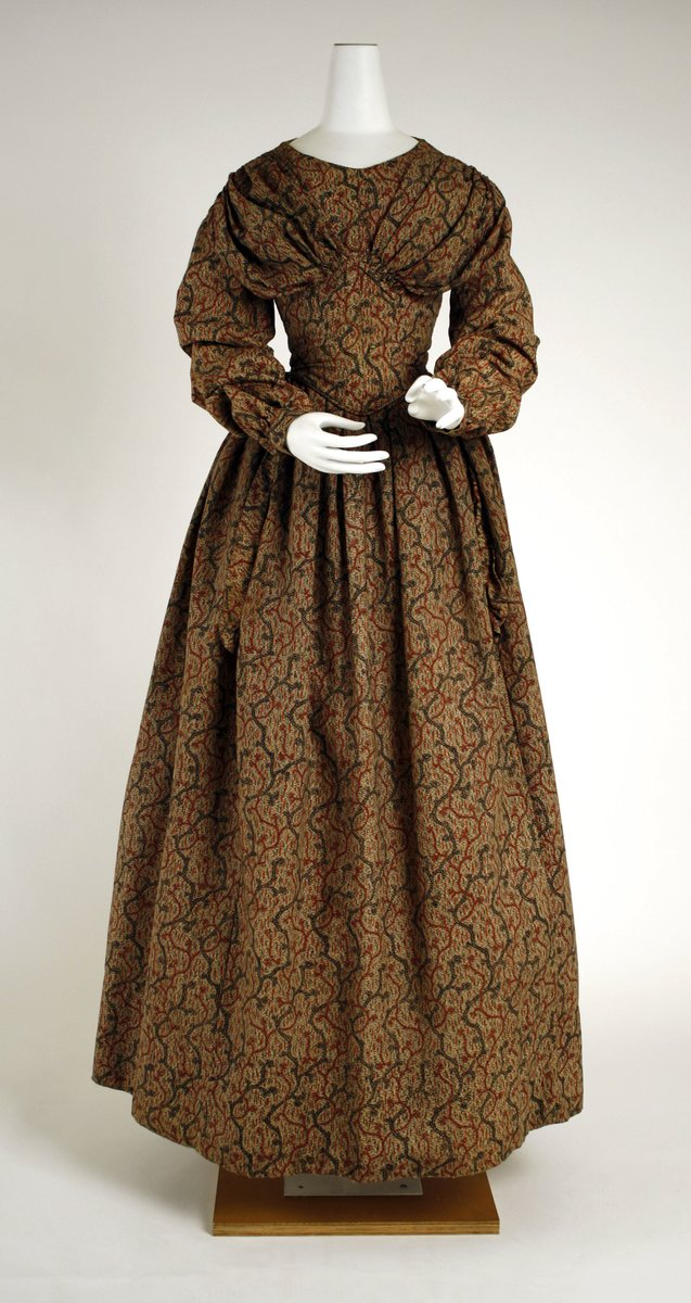Cotton and wool day dress, ruched shoulders and sleeves, but not very puffy. Cinched bodice, more flared skirt. The print is brown, but the design looks like mountains. The colors are browns, reds, and blacks. You can see the shoulders dropping again.