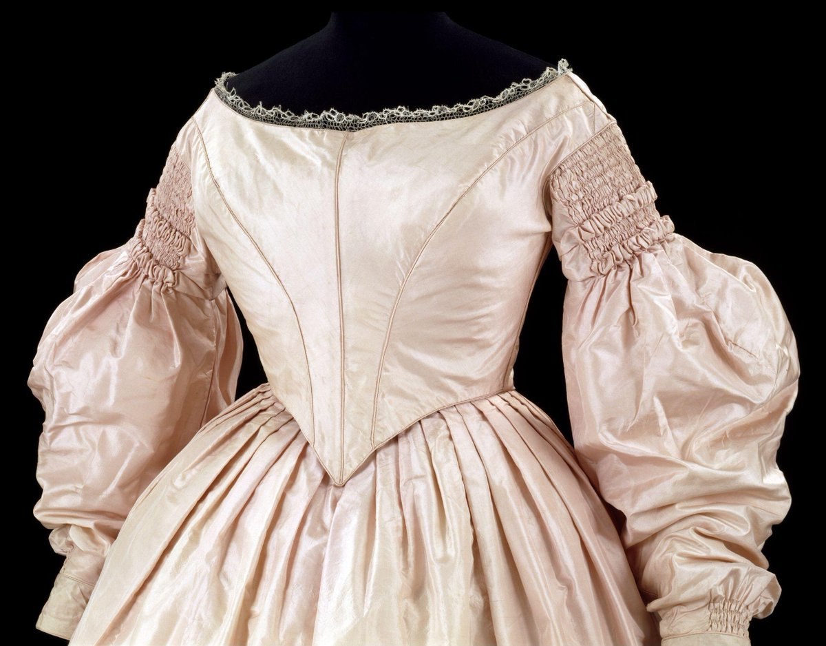 ©Victoria and Albert Museum, London Silk dress consisting of a skirt and bodice, belt, pair of sleeves and pair of dress fragments.    The separate skirt, which has a deep border at the hem, is flat-pleated with a panel of tight gauging at the back. The hem is headed by a narrow rouleau band. The skirt fastens at the centre back with a rectangular brass metal hook and round section eye. It is lined with white glazed cotton.    The bodice is tightly fitted, fastens at the back and has a long pointed waist. With a low round neck and sleeves tightly gauged with two rows of puffed gauging at the shoulder and a full bishop sleeve, held at the wrist by a cuff of self material fastening with two brass metal hooks. The bodice has a point at the centre front and is trimmed at the centre back waist with a small bow of self material. A narrow band of silk braid trims the neck. The bodice fastens at the centre back with bronze rectangular section hooks with worked eyes. There is a bone in the cen