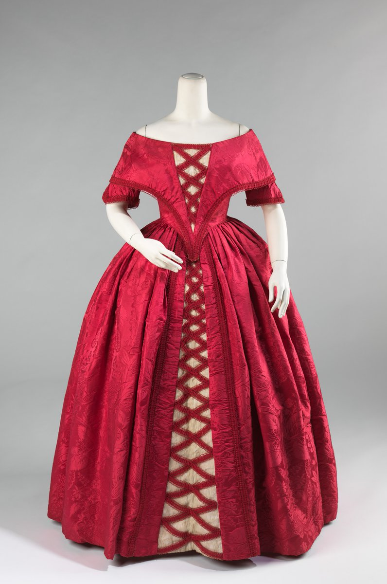 This is a striking example of how 18th-century fabric was treasured. The textile was probably originally a 1740s dress which was taken apart and then reconfigured into this fashionable dress in the early 1840s. The elongated waist and V-shaped bodice front emphasize the bust and wide shoulders and were key features of the dresses of the period. - Via the Met