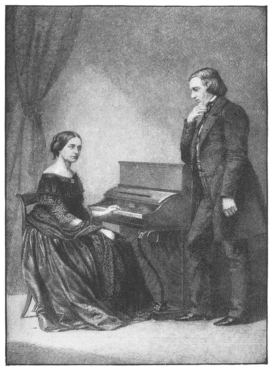 An illustration of Clara and Richard Schumann together, from Clara and Robert Schumann, illustration from Famous Composers and their Works, 1906. She is sitting at the keyboard, while he is standing and looking thoughtful.