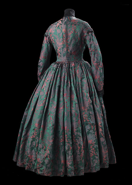Women's dress in green and pink silk woven with a pattern of small pink roses and flowers over larger muted pink stylized foliage against a green background. Bodice with high round neckline, pleated in v-shape from back of shoulder to centre-front edged with black braid and beads, twelve toggles down centre front, fastening centre front and back with hooks and eyes. Three-quarter length sleeves, flared at cuff, trimmed with black braid, lace and beads. Skirt, full-length, pleated into waist. Lined with cotton. Glasgow Museums