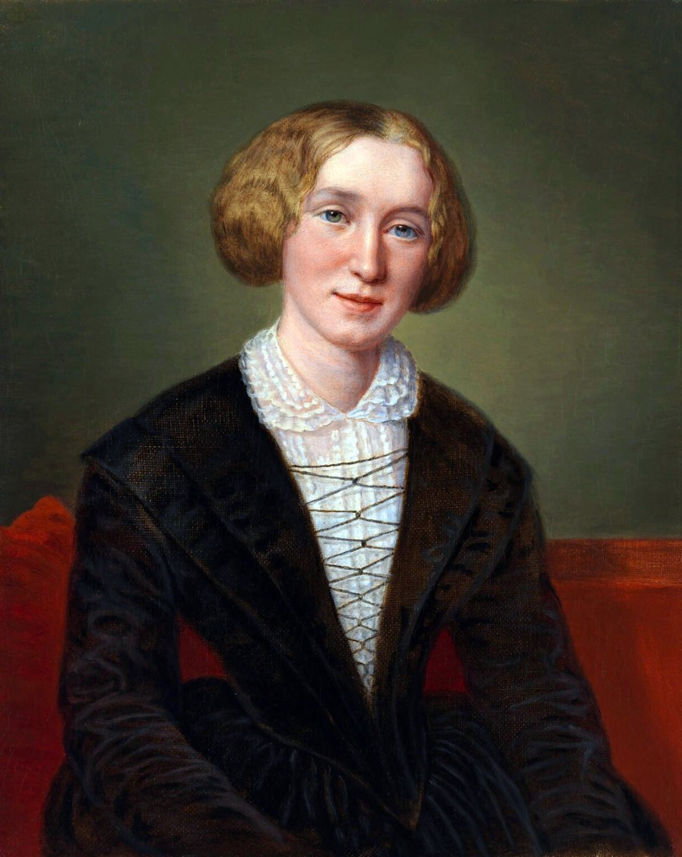 A woman with blonde hair pulled back on either side of her face, blue eyes, and a cleft chin. She wears a black V style gown, with a white blouse beneath, tied with laces across (almost Tudor). It might be velvet.