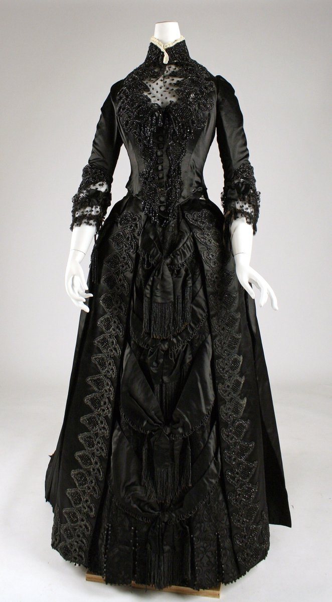 High-collared jet and satin gown, lace at the neck line and sleeves. Extensive embellishment throughout, draping, details. From the Met. Narrow waist.