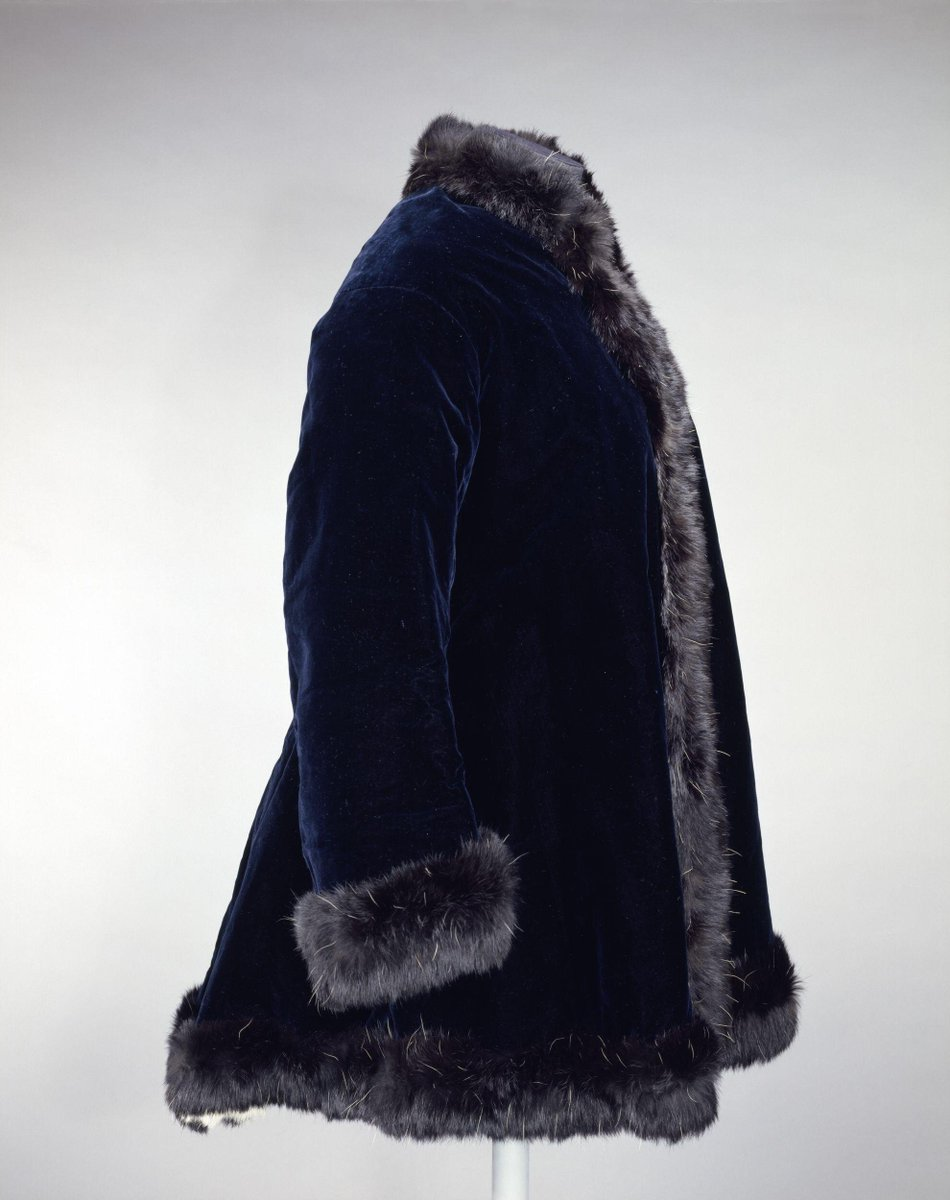 ©Victoria and Albert Museum, London - Woman's jacket, midnight blue velvet, fastened at the front with five sets of hooks and eyes. Shaped at the back with three seams, fitted at the waist. The front opening, neck, cuffs and hem are trimmed with a wide band of black fur applied onto velvet. Lined with ermine.