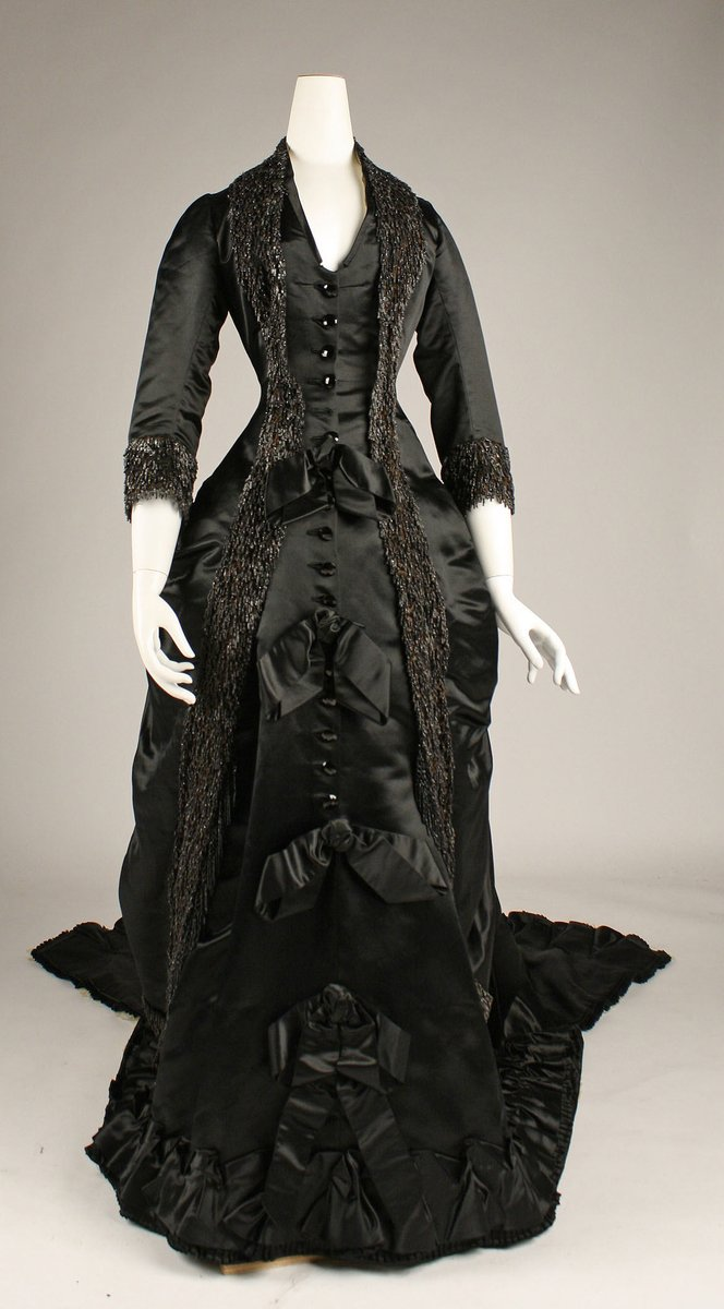 A black satin gown, 1880 silhouette with a narrow waist, V neck, 3/4 sleeves. Long jet tracery stripes down from shoulders to floor. Bows at intervals down the skirt, and buttons down the center.