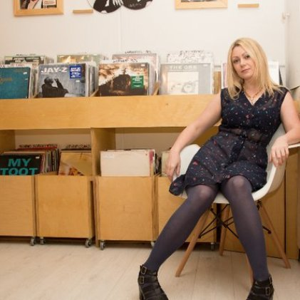 Claire Beck in front of records and sitting on a chair, one of the LGBT+ radio broadcasters to check out on World Radio Day