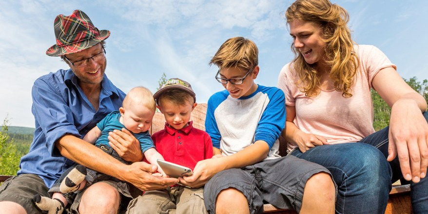 A family looks at a tablet together.