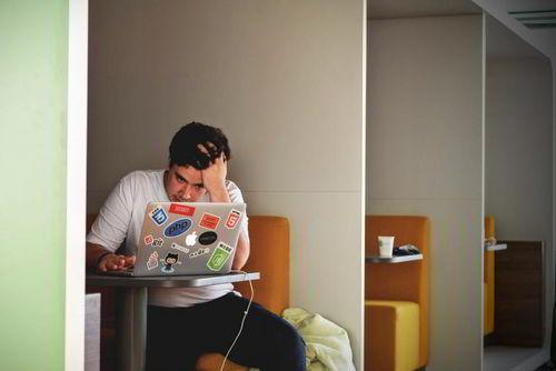 man-zit-verward-aan-laptop Home