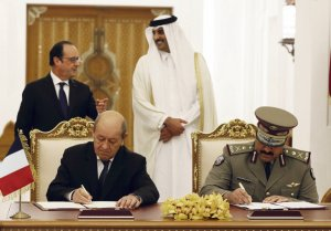 French President Francois Hollande, rear left, and Qatar's Emir Sheikh Tamim bin Hamad Al-Thani, rear right, look on while French defense minister Jean-Yves le Drian, front left, and Qatari Defense Minister Hamad bin Ali al-Attiyah sign the agreement at the Diwan Palace in Doha, Qatar, Monday, May 4, 2015. Hollande signed a 7-billion-euro fighter jet deal and then gets a starring role in a regional summit in Saudi Arabia. Qatar becomes the third buyer of France's delta-winged Rafale, manufactured by Dassault Aviation. (AP Photo/Christophe Ena, Pool)