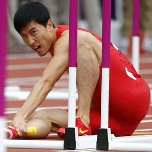 China's Liu Xiang holds his leg after suffering an injury in his