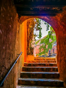 Climbing through a staircase in Rousillon to emerge in a small square