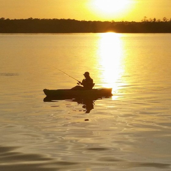 Man on boat in Emerald Isle NC at PDL Beach Properties fishing at sunset with yellow sun shining down on water