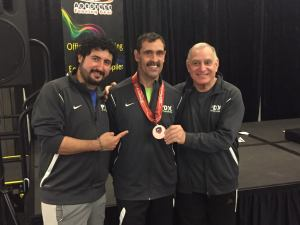 photo of Rick Herrera with his first NAC medal and coaches Hector de la Torre and Charles Randall