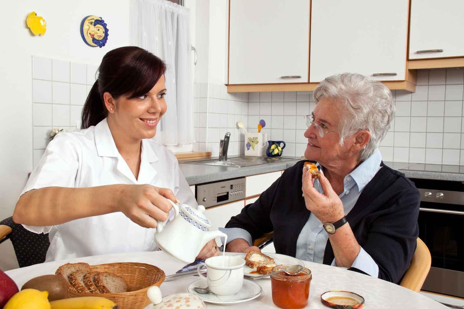 nurse-helps-elderly-woman-at-breakfast-l