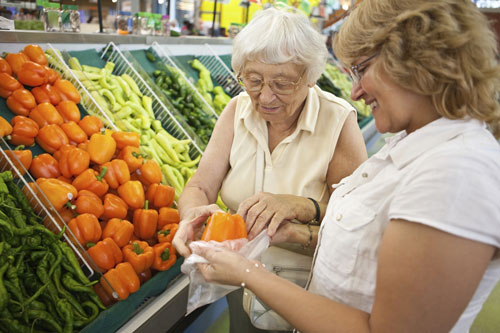 Elderly client and caregiver grocery shopping