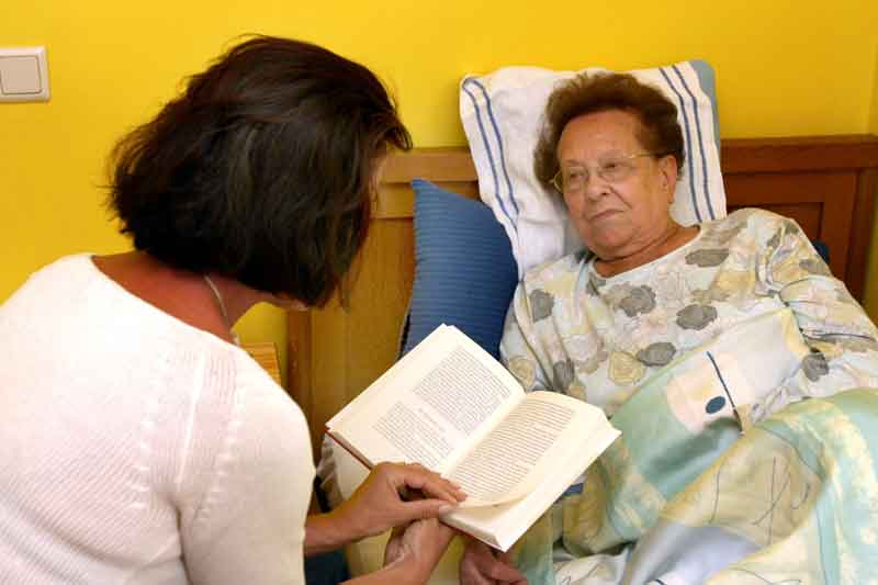 Sick old woman being visited by a friend.