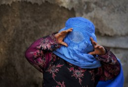 An Afghan girl tries to peer through the holes of her burqa as she plays with other children in the old town of Kabul, on April 7, 2013. (AP Photo/Anja Niedringhaus)