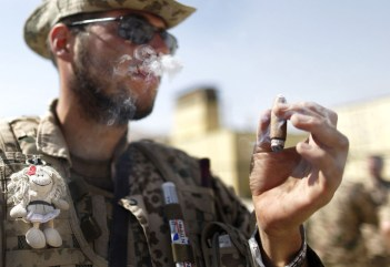 A German ISAF soldier, bearing a lucky charm attached on his bulletproof vest, enjoys a cigar after arriving with his unit back to the base in Feyzabad, east of Kunduz, on September 11, 2009. The unit was stuck for days in the area of Kunduz and came under heavy fire in which four soldiers where injured and evacuated to the field hospital in Kunduz. (AP Photo/Anja Niedringhaus) #