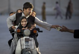An Afghan man with his five children on his motorbike pays money to enter a park in Kandahar, southern Afghanistan, on November 1, 2013. On Fridays, the Islamic day of rest and prayer, children and their families traditionally gather in one of the few parks. (AP Photo/Anja Niedringhaus) #