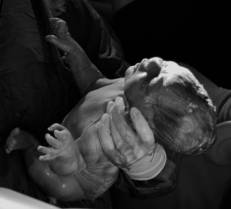 newborn being held up right after delivery in black and white