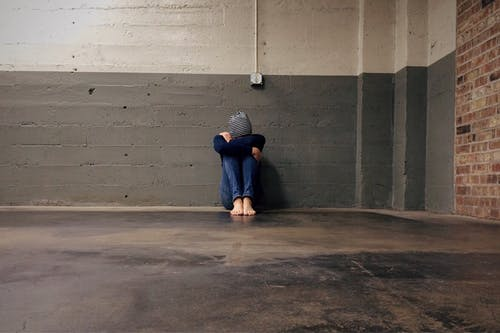 A person all alone in a cement building signifying Peace House as a refuge