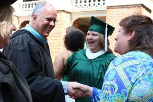 professor christman shaking hands with a parent at graduation ceremony