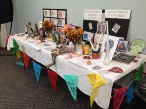 "a table full of ""representations of death and life and offerings to the dead."" Mostly candles, skulls, flags, and flowers. Set up in Flowe 3rd floor for students to walk past and see before going to class. Usually set up every halloween"