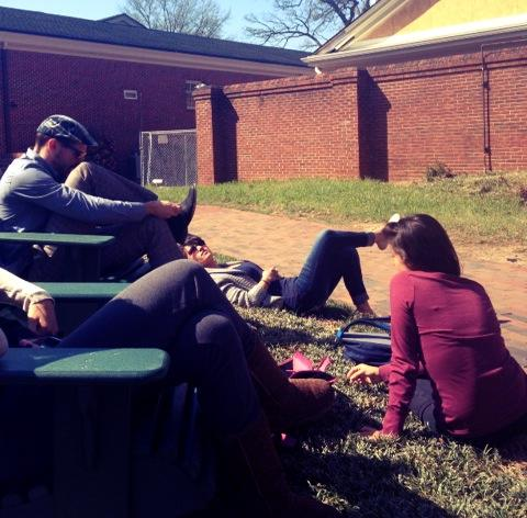 A group of male and female students sitting in the grass