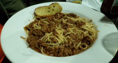 spaghetti, meat sauce and bread on a plate