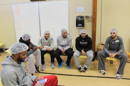 Peace students sit on chairs in a circle wearing hairnets