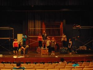 Students stand on stage practicing a performance in an auditorium