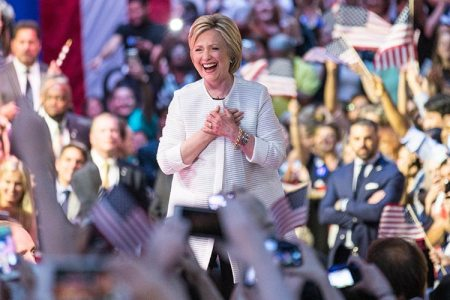 Hillary Clinton stands in the center of a crowd of people waving American Flags