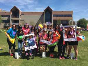 Group of females from Eta Sigma hold frames for Relay for Life dressed in beach attire