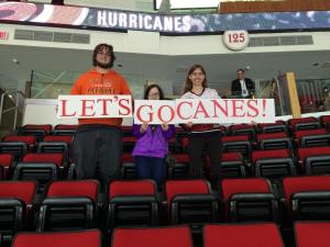 "3 Peace students stand in Section 125 of the PNC Arena holding a sign that reads ""LETS GO CANES"""
