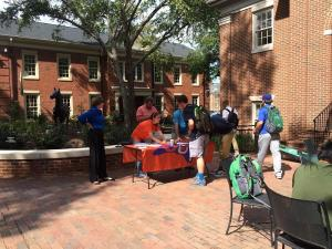 Folding table with orange tablecloth is set up in front of Belk Dining Hall with students gathered around