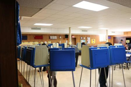 Polling station with blue booths set up in a semi circle in a conference room