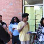 Multiple students stand in single file line with pamphlets in hand entering a brick building