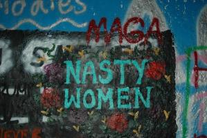 """graffiti on a painted wall with the inscription in blue and red: """"MAGA""""; """"NASTY WOMEN"""", surrounded by graffiti flowers"""
