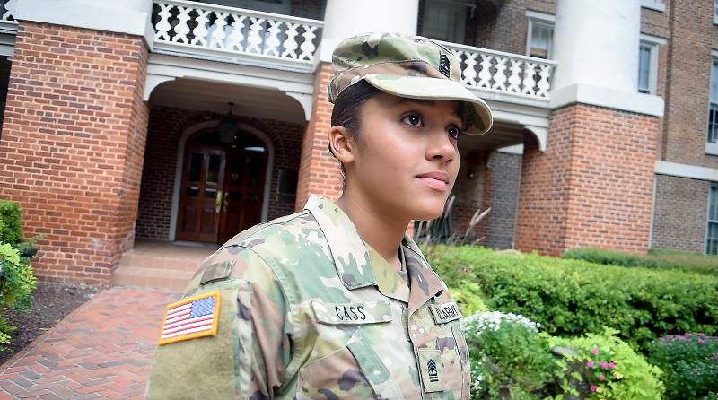 Kristina Cass, female student at WPU stands in front of Main Building dressed in Army colors