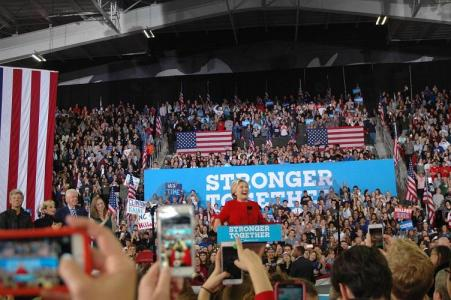 Hillary Clinton stands at a podium in a crowded room framed by American flags and multiple cell phones