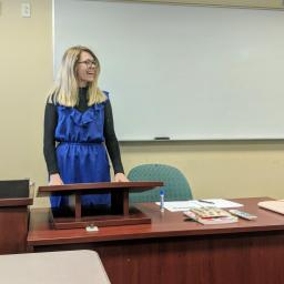 Blonde girl in blue dress speaking in front of a whiteboard with a brown desk and small podium in front of her.
