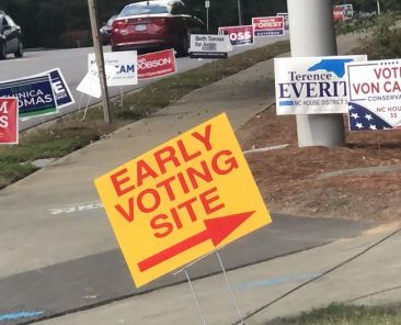 A sign outside of Abbotts Creek Community Center designates the nearby early voting site. It is accompanied by various other signs promoting North Carolina's political candidates. Photo by Photo Courtesy of Jasanee Killins