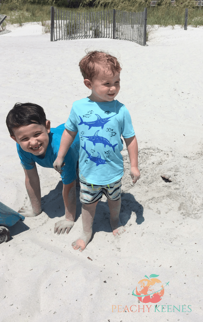 boys playing in sand at Caligny Beach